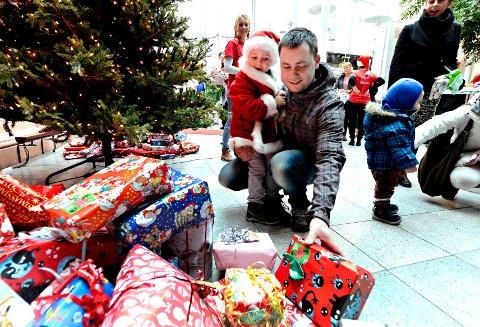 Theodor Alexander Lie Arnesen (3), for anledningen utkledd som julenisse, syntes det var godt å få litt hjelp av pappa Alexander Arnesen da pakken skulle legges i den store gavehaugen i foajeen på teatret i går. Selv gleder treåringen fra Sande seg veldig til jul.
