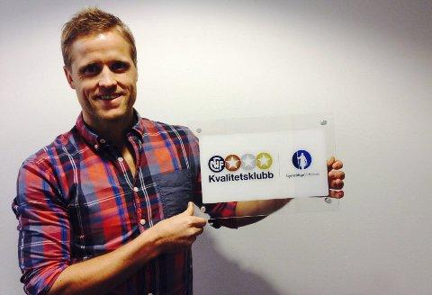 Synlig bevis: Fagansvarlig Kristoffer Paulsen Vatshaug viser skiltet som klubbene på nivå 1 i NFFs Kvalitetsklubb mottar.foto: NFF