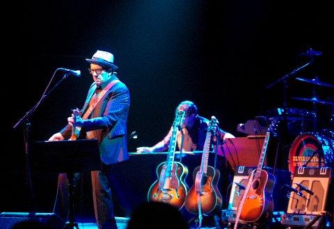 MANGE ANSIKTER: Elvis Costello har mange ansikter - og mange gitarer i ryggen.