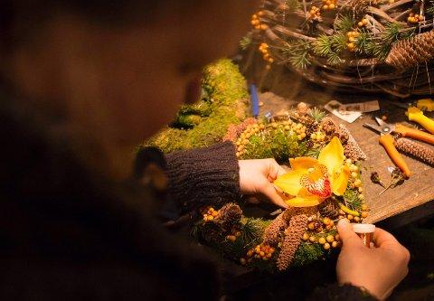 Blomsterdekoratør Marie Victoria Dæhlie synes en adventskrans kan ha mye dekor, og nesten med hva som helst. Her fester hun en orkidéblomst til kransen.
