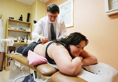 <b>FORT FERDIG</b>: Pasient Ann Kristin Susort ligger ikke lenger enn tre minutter på benken når lege Bjørn Rismyhr behandler henne. – Det er ikke spesielt behagelig, men det går greit selv om jeg ikke liker nåler, sier Susort.