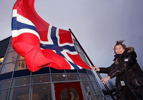 Direktør Ellen Bjerregard ved Oslo Flaggfabrikk «planter flagget» som en illustrasjon av at Rygge-bedriften har produsert det flagget som i dag plantes på Sydpolen. Dermed trekkes linjen direkte tilbake til begivenhetene for 100 år siden, da Roald Amundsen erobret Sydpolen.