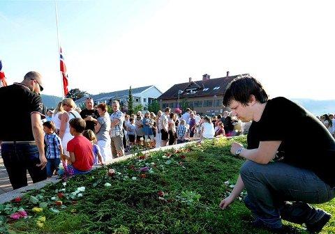 takker: Tore Remi Christensen legger ned roser på torget i Sande etter rosetoget i går kveld. Foto: Sven-Erik Røed
