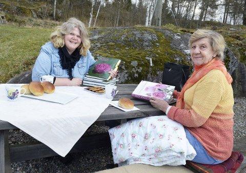 Hanne Dølheim (til venstre) har en tre mål stor hage opp mot skog og jorder, der det også er anlagt flere fine bed. Aase Winger er kommet på besøk for å planlegge aktiviteter i Drøbak/Frogn roseklubb, og de to kvinnene kan gjerne fordype seg i rosebøker.  Foto: Kari Kløvstad