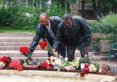 Hassan Ali Nor Ahmed (til venstre) og Mohamed Hasni Diini la mandag formiddag ned blomster ved fontenen i Moss.