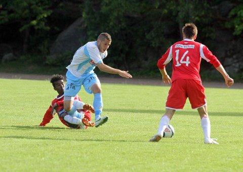 Ruben Valdueza Eiret (i hvitt og blått) blir taklet av Drøbak/Frogns Samale Wais. De to blir lagkamerater fra 1. august. FOTO: KNUT STENSETH