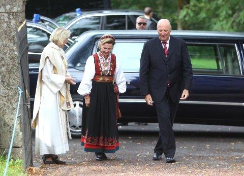 Kong Harald og Dronning Sonja på vei inn i Asker kirke sammen med presten.