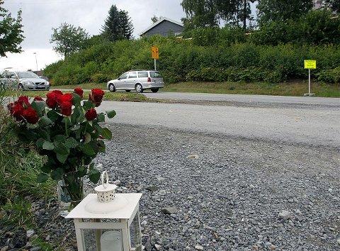 OMKOM: Blomster og tente lys var lagt ned like ved ulykkesstedet der Trude Strømman fra Jar omkom fredag morgen. 56-åringen forsøkte å krysse veien foran en lastebil som kom fra anleggsområdet. FOTO: KARL BRAANAAS