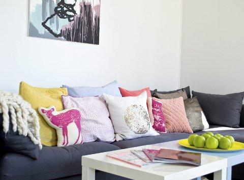 De fargerike putene står i kontrast til de hvite stueveggene og en mer nøytral sofa.
