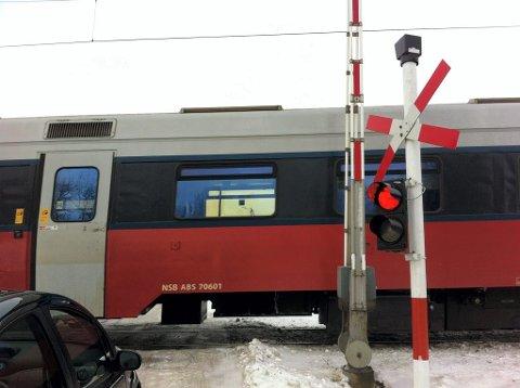 Her kjører toget forbi overgangen ved Råstad stasjon med bommen oppe.
