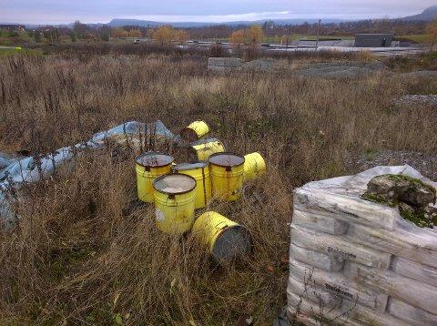 De ni gule tønnene er synlige, der de ligger i terrenget like ved Festplassen i Nansenparken på Fornebu (bak).