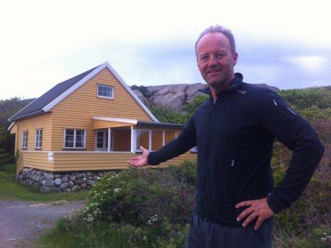 Espen Løkkevol foran hytta i Folehavna. Banksjefen hadde håpet hytta ble kjøpt av turistforeningen - men slik ble det ikke.