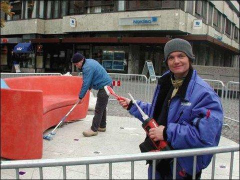 Opphavskvinne Helena von Bergen og Leo Tiggelman fra firmaet Contiga i bakgrunnen i ferd med å klargjøre sofakroken av betong i gågaten.