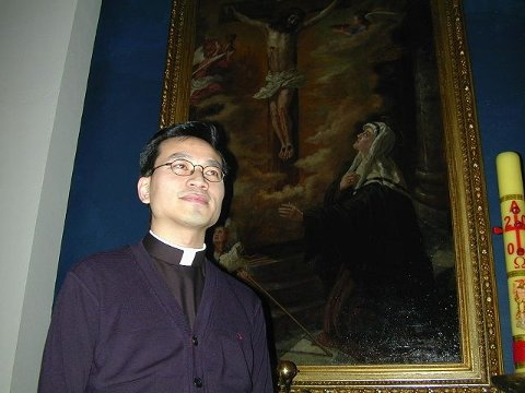 TJENESTE: Pater Nguyen Tuan Van ved siden av et av de talende maleriene i kirken hvor han nå er prest.