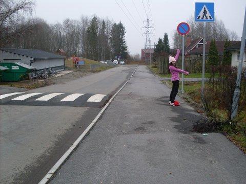 Behin viser skilt ved gangfelt ved Finstad skole