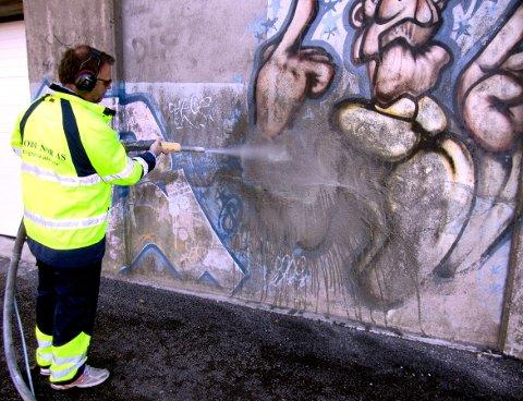 Vekk med taggingen. Roger Arnesen jobbet i ettermiddag effektivt med på fjerne taggingen under Fredrikstadbrua. Foto: Tore Tindlund