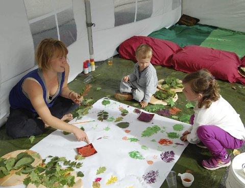 LØVTRYKK: Anna Austad fra BUA viser Eiriana (6) og Elliott (3) hvordan de kan male på blad og trykke mønster.