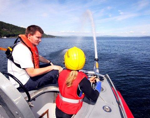 STRÅLENDE: Ylva Mathisen (11) frydet seg over å styre vannkanonen på båten. Andre Olstad passer på sikkerheten.