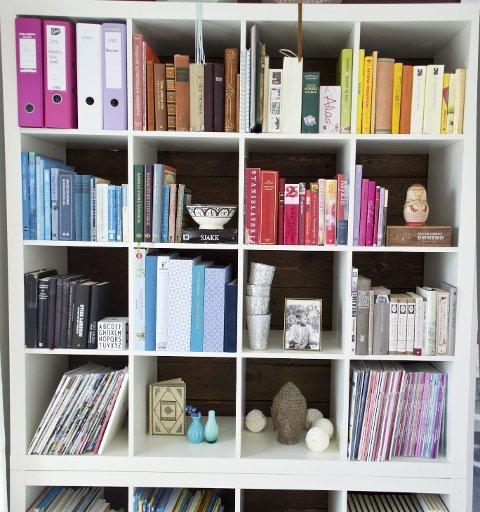 Bøkene i bokhylla er sortert etter farger.