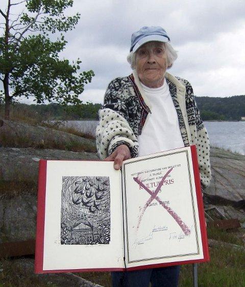 Forfatter Karin Bang har hatt 30 år som sommergjest på Veierland og bodd der fast i over 50. Hun er ikke fornøyd med hvordan Nøtterøy kommune har håndtert bopliktsaken. Lørdag protesterte hun ved å kaste kulturprisen på sankthansbålet.