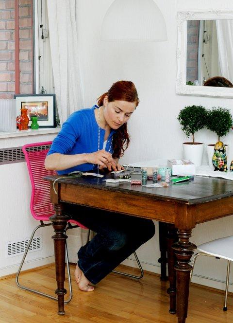– Jeg liker å gjøre det litt spesielt, sier Signe Schineller. Her lager hun bordkort og presangkort av gamle merkelapper og litt glitter.