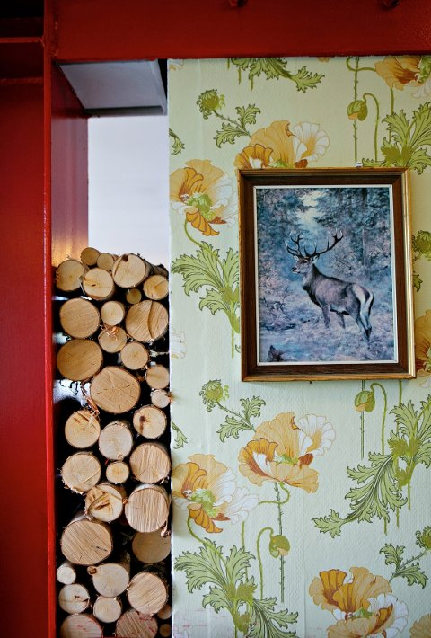 Retrotapet, vedkubber og bilde med skogsmotiv skal på kafeen Kanskje kommer kongen gi assosiasjoner til bestemors stue.