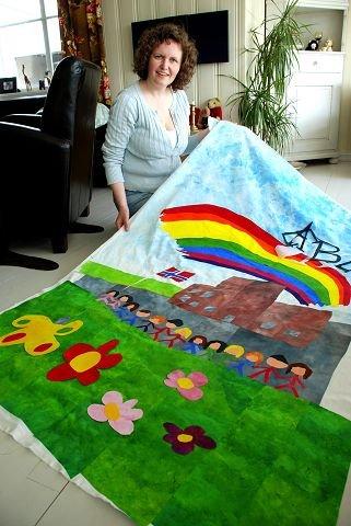 Tove Stang Karlsen mangler bare å få på bokstavene og litt finpuss før fana il Nes barneskole er klart til bruk på nasjonaldagen. (Foto: Jeanette Sandbæk Håland).