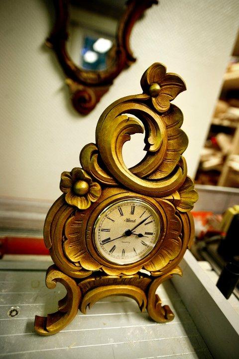 Både barokk- og rokokkostil er basert på akantusmønsteret. Rokokko skiller seg fra barokken med asymmetriske skjell og blomster. Her sees rokokkoklokke til cirka 2000 kroner.