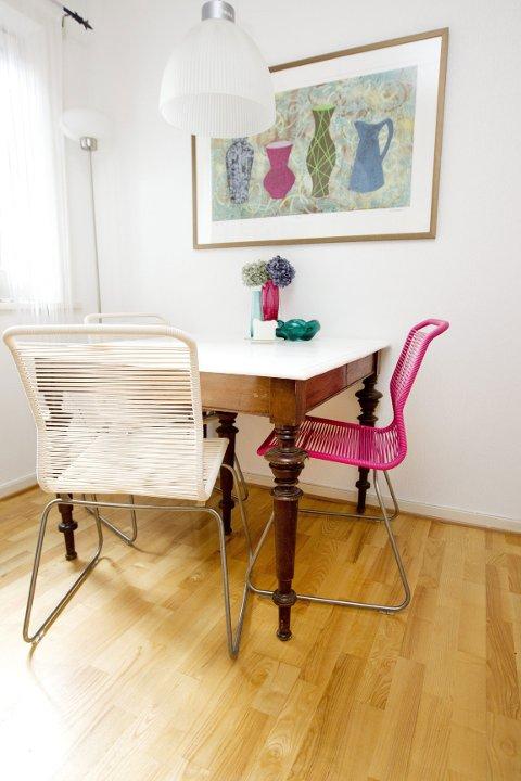 Gammelt bord med nymalt bordplate, nye stoler, brukte vaser, bilde som fikk ny plass da vasene kom i hus, og ei kvalitetslampe som lå øverst i en konteiner.