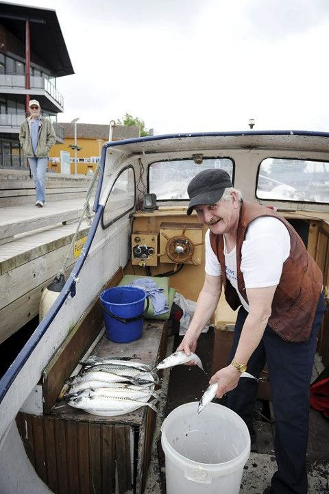 Ole Høisæt fikk makrell på kroken i dag morges. I sjøen langs bryggene inne i Byfjorden kokte det av både makrell og måker på sildejakt.