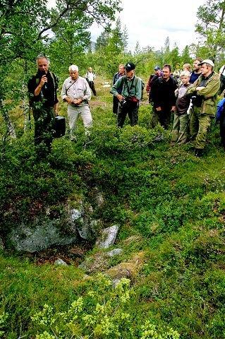 FANGSTGRAV: Per Olav Mathiesen(t.v.) som forklarer for et lyfhørt publikum ved ei av de mange fangstgravene i systemet nord for Storlegda, og som mener at dette kan være fra 1200-tallet. $BYLINE_ON$Foto: Per Ivar Strømsmoen$BYLINE_OFF$