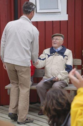 """Jubilanten: Her overrekker dirigent Arne Kollandsrud en kopi av den nyarrangerte marsjen """"Mosktraumen marsj"""" til komponist Asbjørn J. Helle. Helle skrev opprinnelig stykket for trekkspill, men marsjen ble arrangert for korps av Jon Rørmark spesielt for turen til Nord-Norge. Den ble urfremført for komponist Asbjørn J. Helle i forbindelse med hans 90 års-dag."""