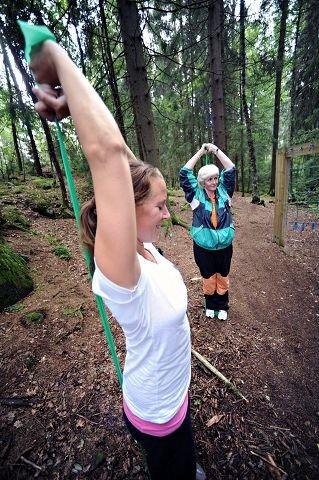 Lederen av Frisklivssentralen, Lene Martinsen Østby, har tatt et godt tak i strikken og viser hvordan ryggøvelsen skal gjøres. Mette Sørlie henger med. Hun har hatt hjerneblødning og trener for å kunne holde seg i jobb.