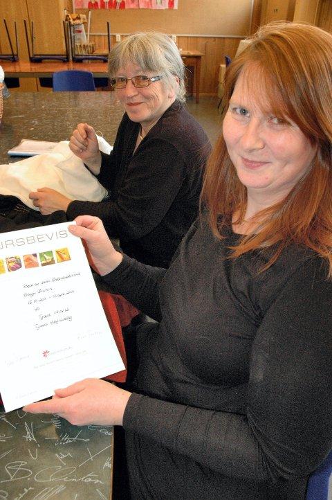 STOLT: Steffi Buron med diplomet som viser at hun har gjennomført kurset i norsk bunadssøm. I bakgrunnen sitter Rigmor Tollan som syr Kverbergskjorte til Steffi.