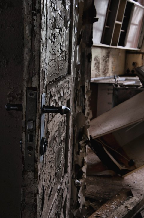 Tapetet henger i store laser på veggene, mens malingen flasser av dørene.