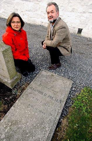 Jølsens grav: Ragnhild Jølsen er gravlagt her ved Enebakk kirke. 100 år etter hennes død 28. januar 1908, blir det avduket et smijernskors på graven. På bildet: Grete Dihle, kirkeverge og Per Sandvik, kultur- og oppvekstsjef i Enebakk kommune.