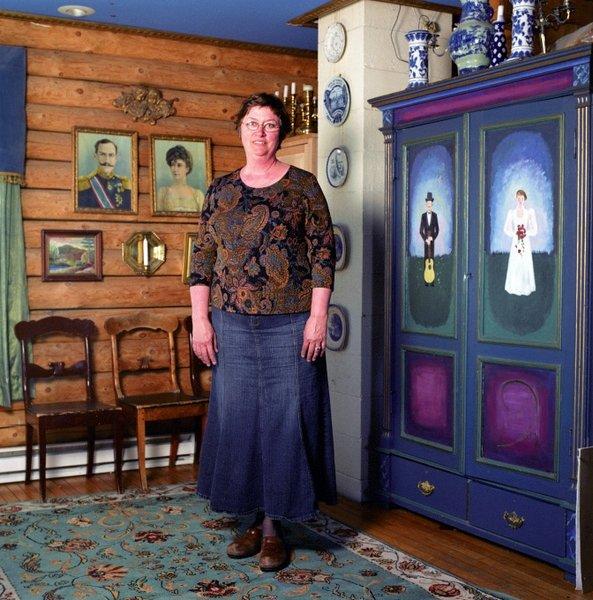 Hjemme hos Arna Rennan i Duluth henger kongefamilien, landskapsbilder, og pyntefat med norske eventyrere på tømmerveggen.